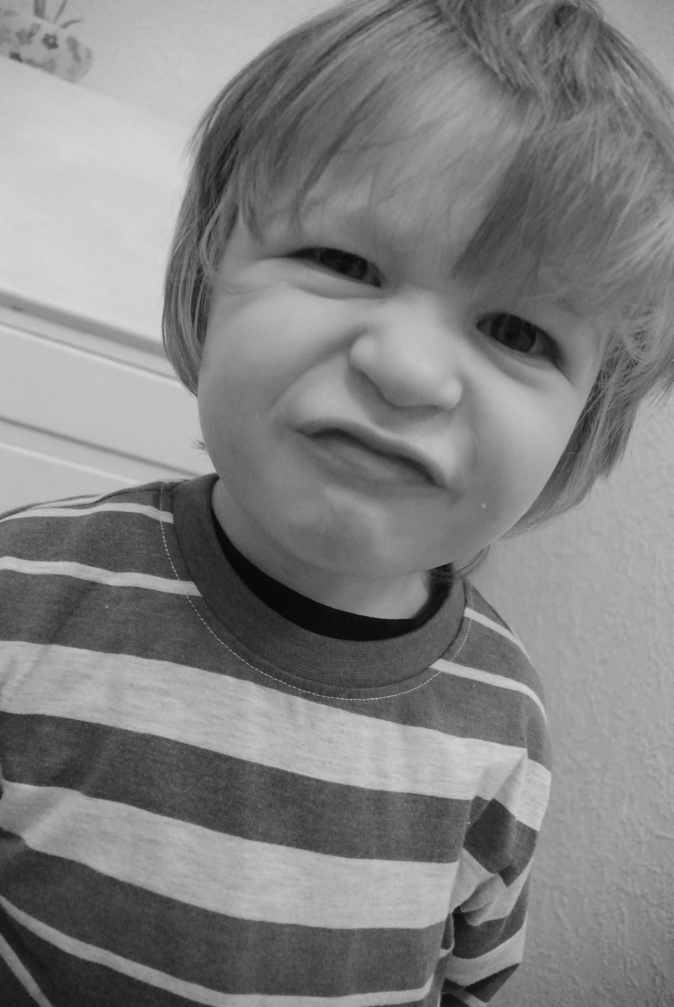 Black and white picture of a four year old boy in a striped top pulling a grumpy face.