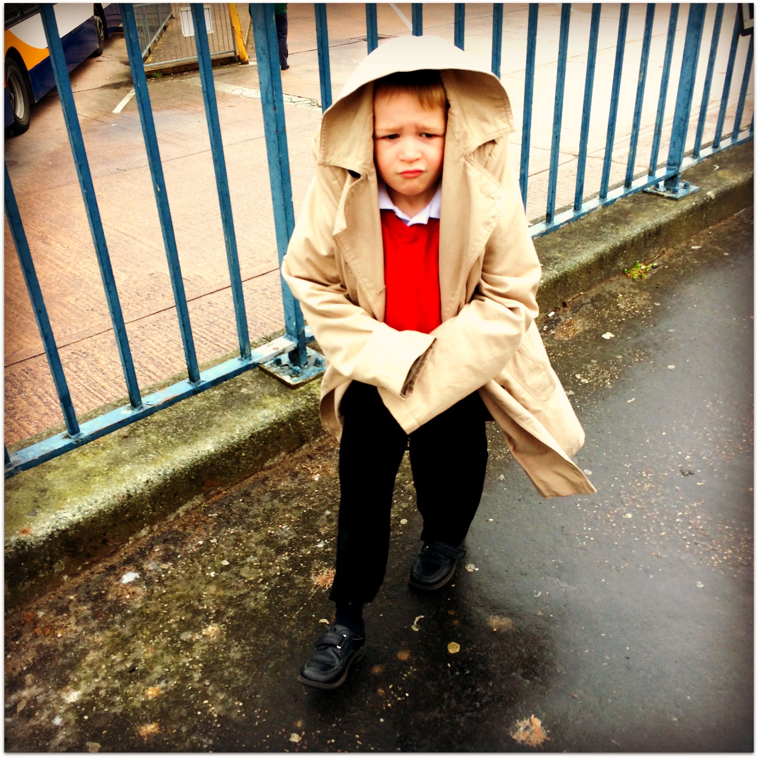 Picture of a little boy in a red jumper with a sad look on his face wearing a womans coat over his head
