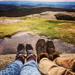 Small image of two people's muddy walking boots in the foreground with the hills and sky behind on a sunny day.